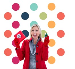 Composite image of festive blonde holding gift and credit card