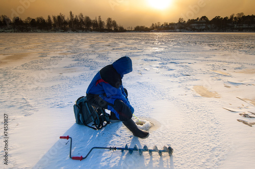 Staande foto Vissen Ice fisher with ice auger