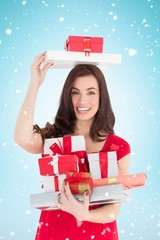 Composite image of smiling brunette holding many gifts