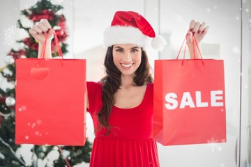 Composite image of brunette showing sale bag and shopping bag