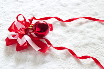 Red ribbon and christmas ball on snow background