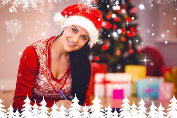 Composite image of festive brunette writing her list