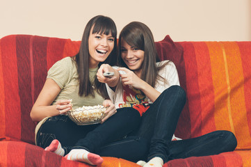 Students - Two smiling female teenager watching television