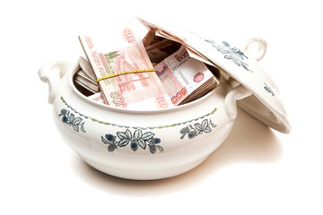 Пачки российских денег в супнице на белом фоне