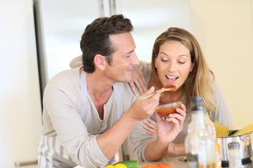 Man having woman tasting tomato sauce