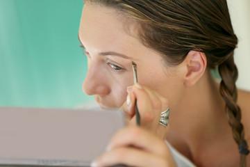 Woman applying makeup on her eyebrows