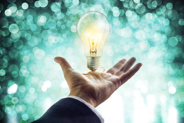 Hands of a businessman reaching to towards light bulb