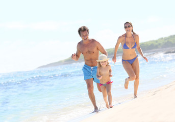 Family running in swimsuit on a Caribbean beach