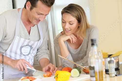 canvas print picture Woman watching husband preparing pasta dish
