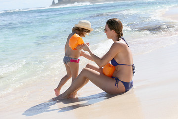 Mother putting swimming armbands to little girl at the beach
