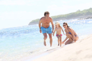 Family of three playing on a sandy beach in summertime