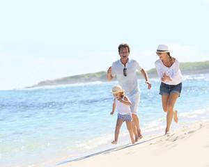 Couple with little girl running on Caribbean beach