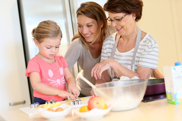 Little girl with mom and grandmother baking cookies at home