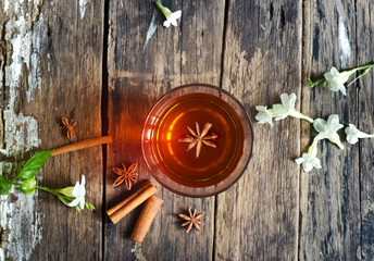 star anise in tea glass vibrant on wooden and cinnamon backgroun