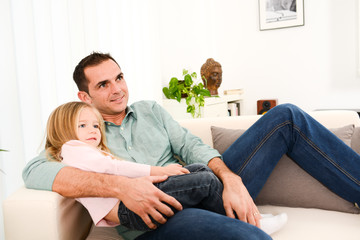 happy handsome young daddy and young daugther on sofa at home