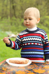 funny boy eats sausages on picnic