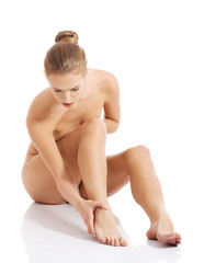Nude woman sitting, touching her foot bone