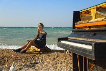 beautiful girl with notes from an old piano on the beach