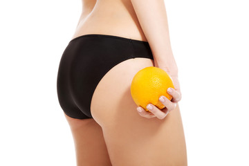 Close up on woman in panties holding yellow mango