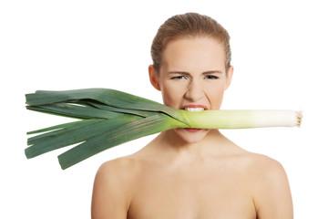 Portrait of nude woman eating leek