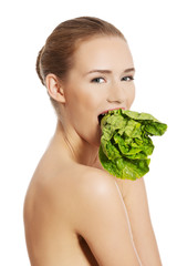 Side view of nude woman eating lettuce