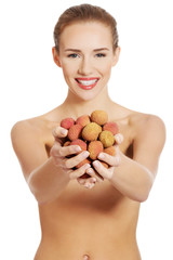Portrait of a woman holding lychees