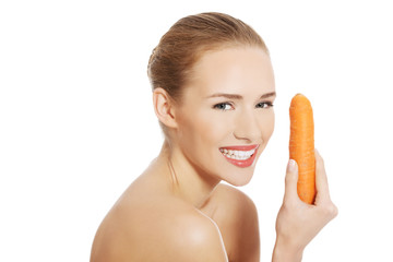 Portrait of nude woman holding a carrot