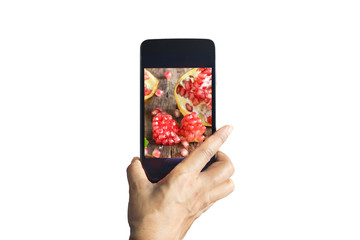 Smartphone take photos of pomegranate on isolated background,