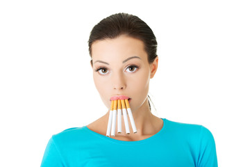 Young woman with group of cigarettes in mouth