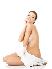 Side view nude woman sitting wrapped in towel