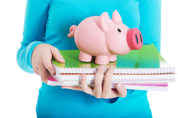 Close up on a piggybank and notebooks