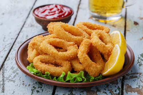 Fotobehang Schaaldieren fried squid rings breaded with lemon