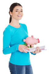 Happy woman standing with piggybank and notebooks
