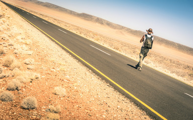 Lonely man walking along the road among african desert