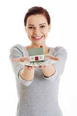 Happy woman holding house model and dollar bills