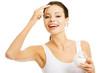Portrait of beautiful woman applying cream on face