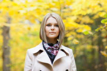 Serious young woman in autumn forest