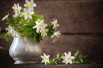 snowdrops in vase  on wooden background