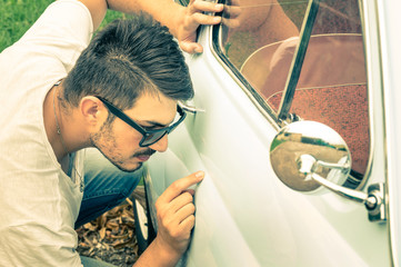 Young handsome man with sunglasses inspecting a vintage car body