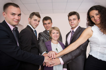 Six business people join hands and smiling
