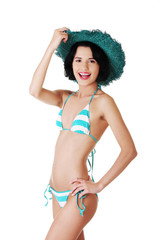 Young slim woman wearing swimwear and summer hat