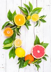 Fresh citrus fruits on white wood background. Letter c fruits.