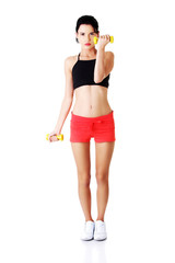 Full length woman exercising with dumbbells