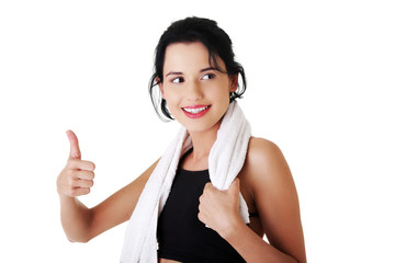 Young happy sportswoman showing thumbs up