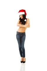 Full length woman shirtless wearing santa hat