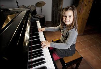 Nina de ocho anos feliz tocando el piano