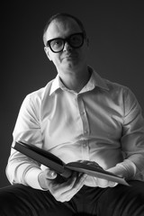 Portrait of middle aged man with open book, monochrome