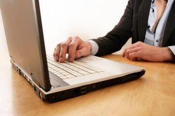 Mann tippt auf Tastatur