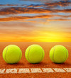 Tennis balls on a tennis clay court in the sunset