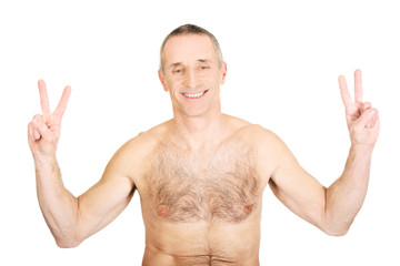 Portrait of mature shirtless man with victory sign